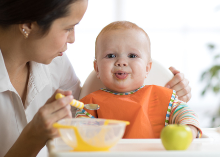 Mother feeds her kid. Baby is crying, capricious and refusing to eat