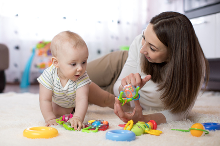 Adorable baby boy playing with educational toys in nursery. Happy healthy child having fun with colorful different toys at home.