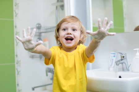 Cheerful child washing hands and showing soapy palms