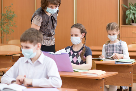 school children with protection masks against flu virus at lesson in classroom