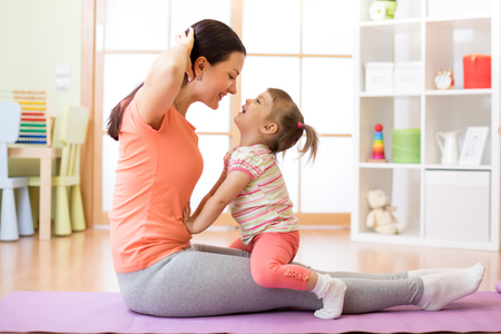 Mother and child toddler engaged in fitness, yoga, exercise at home Stock Photo