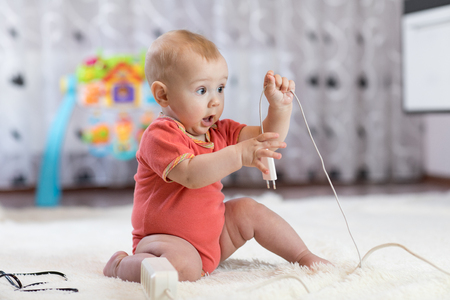 Funny baby boy pulling cables from electrical extension Stockfoto
