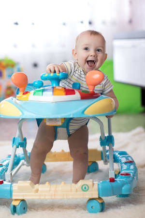 cheerful baby boy in the baby walker in living room 스톡 콘텐츠