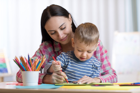 Mother and child son drawing with colored pencils Foto de archivo