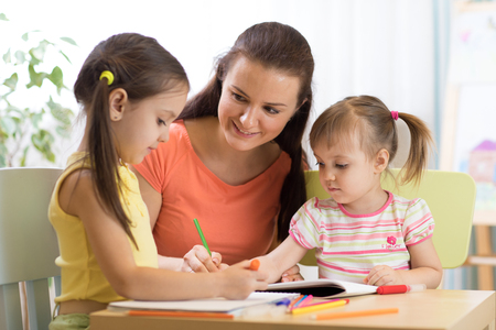 Woman and children girls drawing with colored pencils Stock Photo