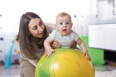 Woman doing exercises on a fit ball with baby.