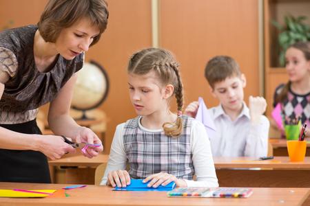 School children working at labour lesson. Teacher helping pupil.