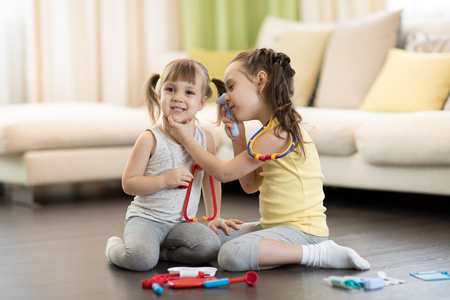 Two happy children, cute toddler girl and her older kid sister, playing doctor and hospital using stethoscope toy and other medical toys, having fun at home