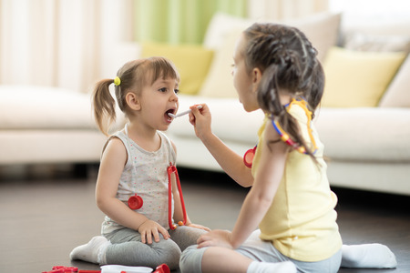 Two kids girls playing doctor at home. Toddler girl opens her mouth and says aaah. Child girl examining little sister.