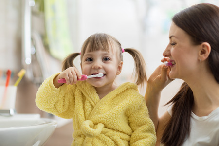 Beautiful mother and kid daughter brushing teeth in bathroom