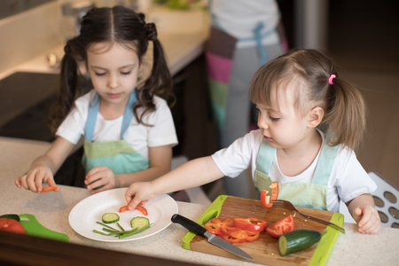 Cute children helping mother at kitchen. Adorable kids sisters making funny face with vegetables on plate.