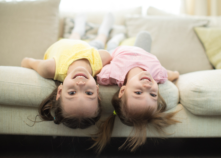 Portrait of two smiling children sisters lying upside down on sofa in living room at home Stockfoto