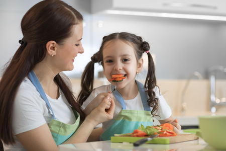 mom feeding child daughter vegetables in kitchen