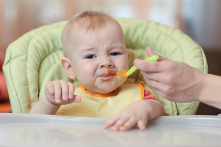 Cute baby refusing to eat food from spoon with face dirty of vegetable puree.