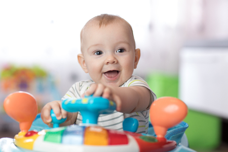 Portrait of baby boy playing in baby walker Banque d'images