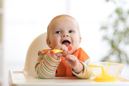 happy baby boy waiting for food with spoon at table Banque d'images
