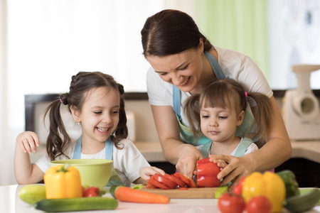 Happy mother and her daughters enjoy making healthy meal together at their home