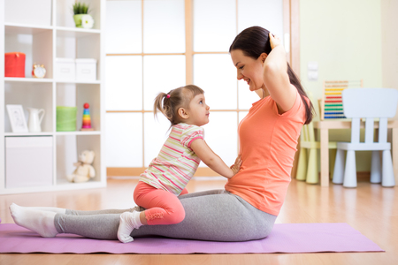 Mom and child doing fitness exercises on mat at home