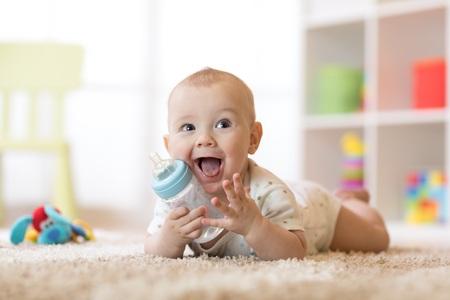 Ładny chłopczyk pije z butelki. Uśmiechnięte dziecko ma 7 miesięcy.