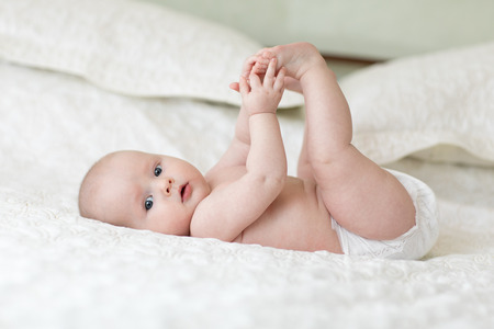 cute baby lying on white sheet and holding his legs