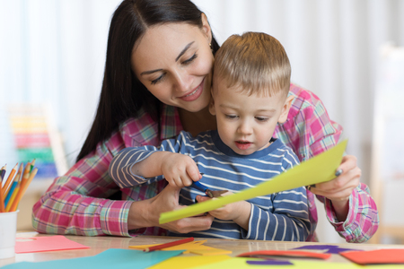 Mother helping her child to cut colored paper
