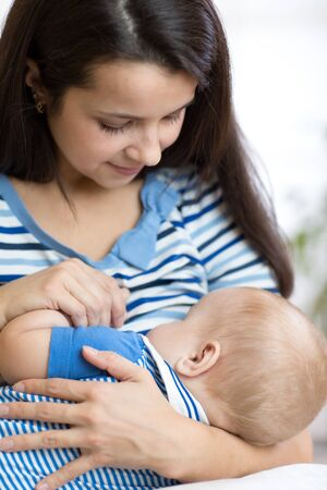 Young mother holding baby. Mom nursing child. Woman breast feeding newborn kid. Banque d'images