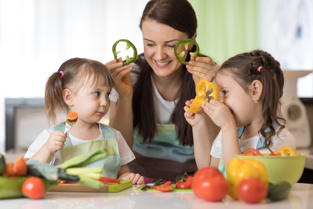 Happy family mom and kids having fun with food vegetables at kitchen holds pepper before their eyes like in glasses