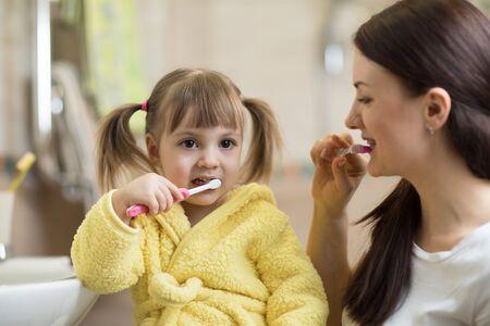 Little child girl brushing teeth in bath