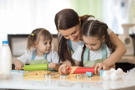 Cute little kids and their beautiful mom in aprons are playing and laughing while kneading the dough in the kitchen Stock Photo