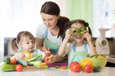 Mom teaches two daughters to cook at the kitchen table with raw food Banque d'images