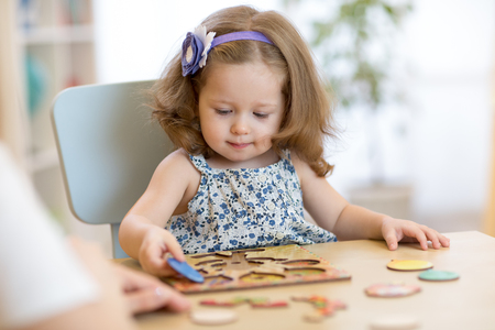Small toddler or baby kid playing with puzzle shapes on low table in children room in nursery or preschool.