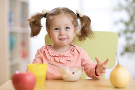 Cute little girl with healthy breakfast at table in kitchen Stock Photo