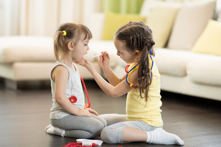 Child girl, playing doctor with her little sister at home in living room Banque d'images