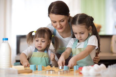Mother and kids daughters in kitchen making cookies. Stock Photo