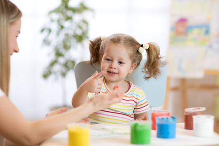 Mother and little daughter kid have a fun pastime with finger pints