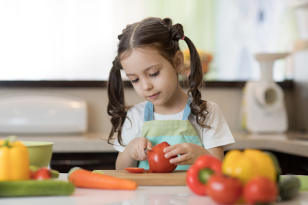 Adorable little girl helping at kitchen with salad making Stock Photo