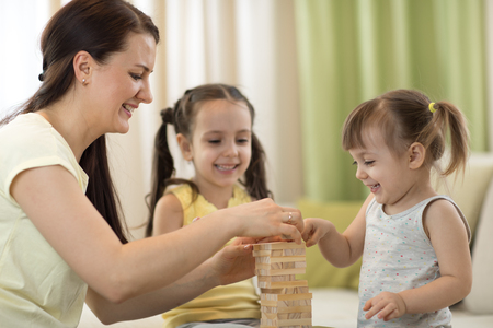 Happy family playing jenga together at home. Mom and daughters having fun in living room.