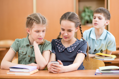Schoolkid girl shows cell phone to friends