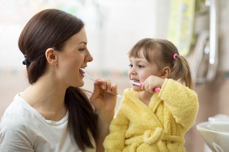 Mother teaching daughter child teeth brushing in bathroom