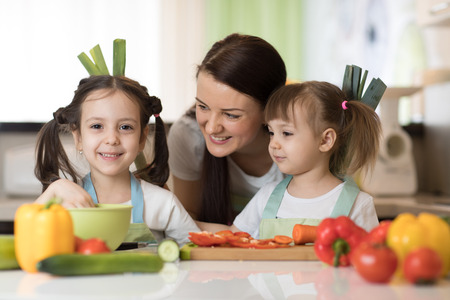 mother and kids daughters having fun in the kitchen Stock Photo
