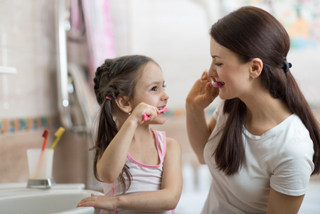 Little child girl and mom brushing teeth in bath Banque d'images