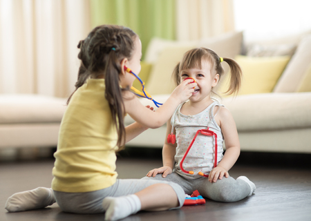 Children girls playing doctor at home