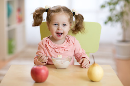 Happy smiling kid eating oatmeal with fruits. The concept of healthy breakfast for children. Banque d'images