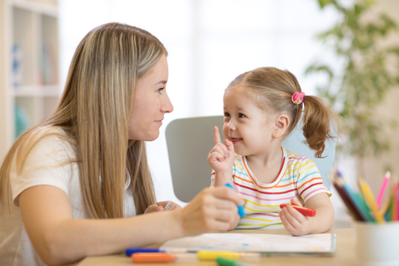 Little child girl coloring with felt pen next to her mother in living room.