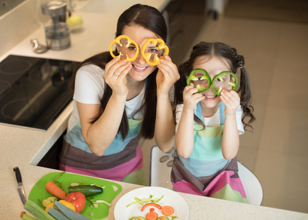mother and kid daughter having fun in the kitchen