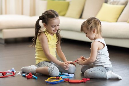Little child girl playing doctor with her younger toddler sister in living room Banque d'images