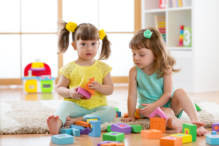 kids playing with developmental toys at home or kindergarten or playschool