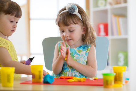 Children creativity. Kid sculpts from clay. Cute little girl moulds plasticine on table 스톡 콘텐츠