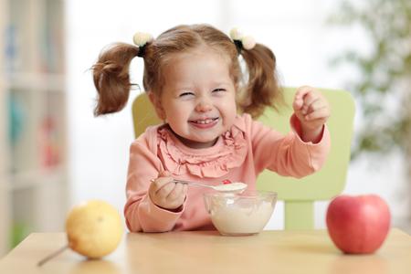 cute child girl eating breakfast at kindergarten.