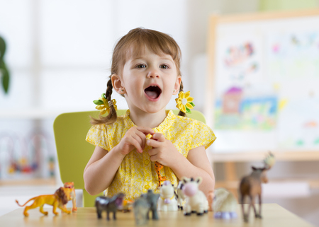 Happy little toddler girl plays animal toys at home or daycare centre
